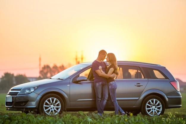 Młoda para, szczupła atrakcyjna kobieta z długimi włosami i przystojny, sportowy mężczyzna stoją razem w srebrnym samochodzie w ciepły letni wieczór na jasnym niebie o zachodzie słońca
