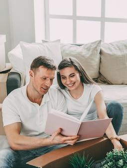Młoda para szuka rodzinnego zdjęcia w nowym mieszkaniu