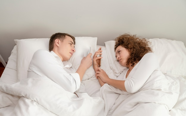 Młoda para szuka smartphone na łóżku.