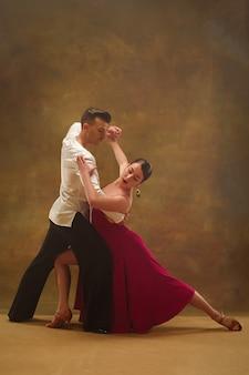 Młoda para tańca towarzyskiego w złotej sukience taniec w zmysłowej pozie na tle studio. profesjonalni tancerze tańczący tango. koncepcja tańca towarzyskiego. ludzkie emocje - miłość i pasja