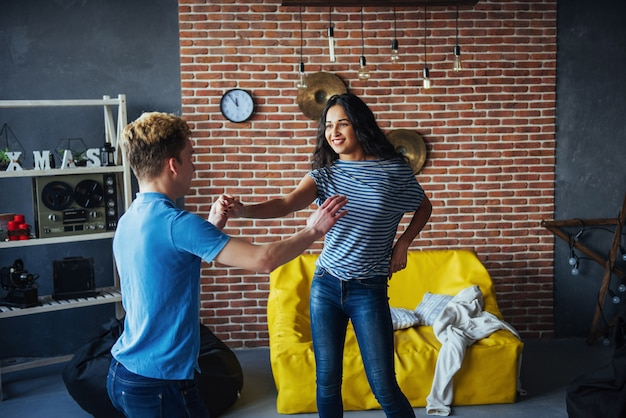 Młoda para tańczy muzykę latynoską: bachata, merengue, salsa. dwie eleganckie pozy w kawiarni z ceglanymi ścianami