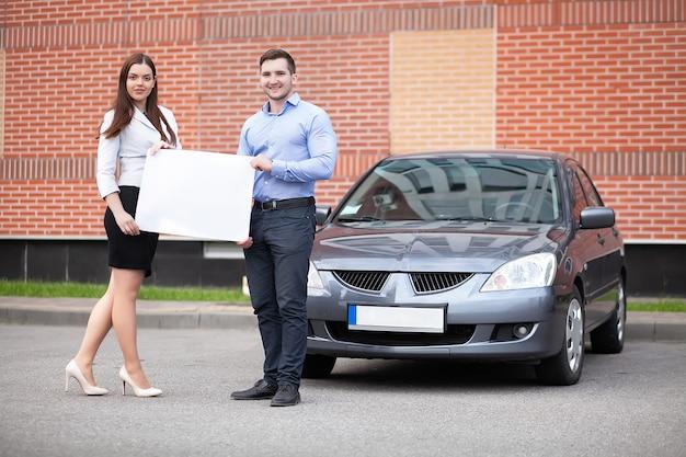 Młoda para trzyma białą kartkę na powierzchni samochodu