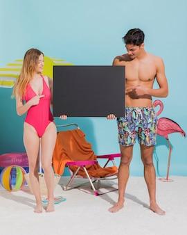 Młoda para trzyma ciemną pustą kartę na plaży