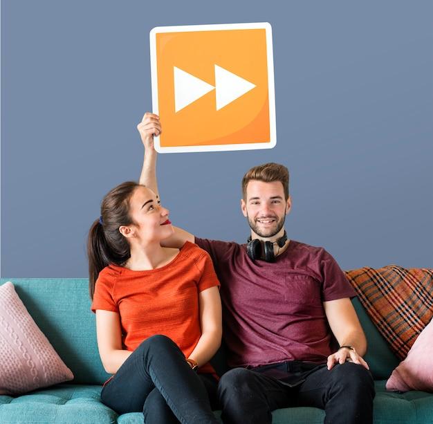 Młoda para trzyma ikonę przycisku szybkiego do przodu