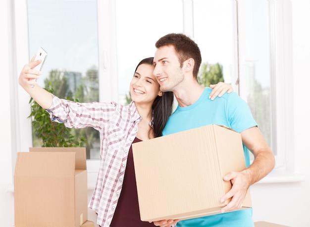 Młoda para trzyma pudełko i uśmiecha się szczęśliwie do kamery.
