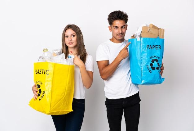 Młoda para trzyma torbę pełną plastiku i papieru na białym tle, wskazując na bok, aby przedstawić produkt