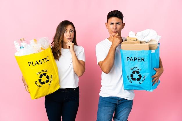 Młoda para trzyma torbę pełną plastiku i papieru na różowo, ma wątpliwości i myśli