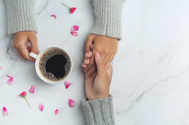 Młoda para trzymając się za ręce do jedzenia kawy na drewnianym stole.