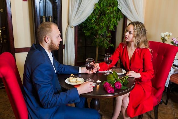 Młoda para trzymając się za ręce przy stole z ciasta