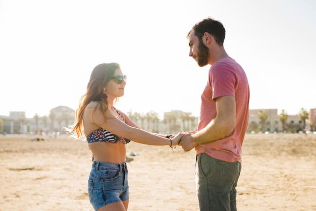 Młoda para trzymając się za rękę stojąc na plaży