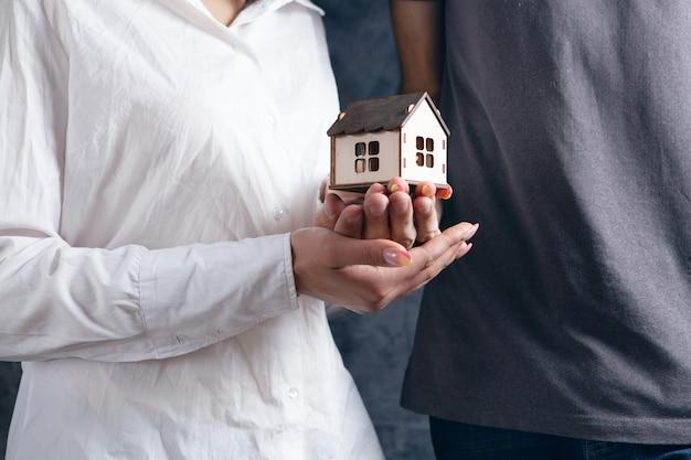 Młoda para trzymająca dom w dłoniach