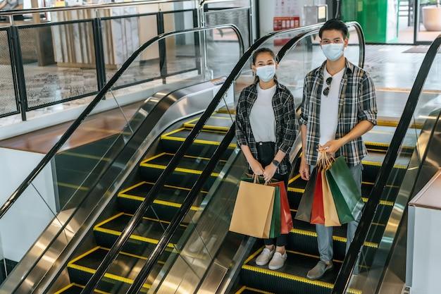 Młoda para trzymająca kilka papierowych toreb na zakupy