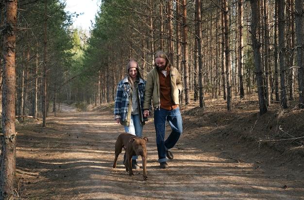 Młoda para trzymająca się za ręce i idąca razem z psem po parku