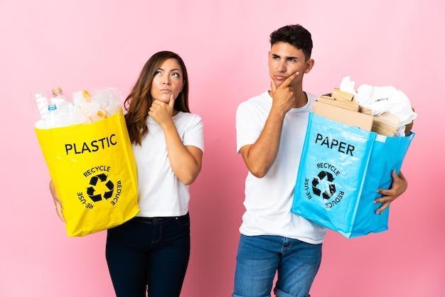 Młoda para trzymająca torbę pełną plastiku i papieru na różowo ma wątpliwości