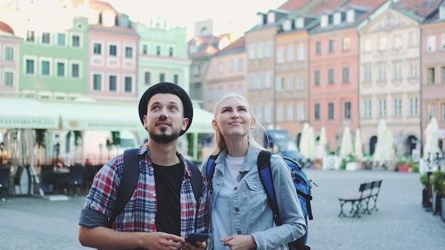 Młoda para turystów korzystających ze smartfona i podziwiających piękną okolicę