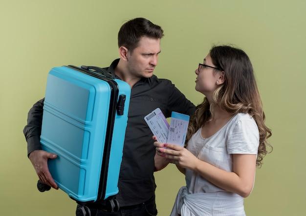 Młoda para turystów, mężczyzna i kobieta, trzymając walizkę i bilety lotnicze, patrząc na siebie niezadowoleni stojąc nad jasną ścianą