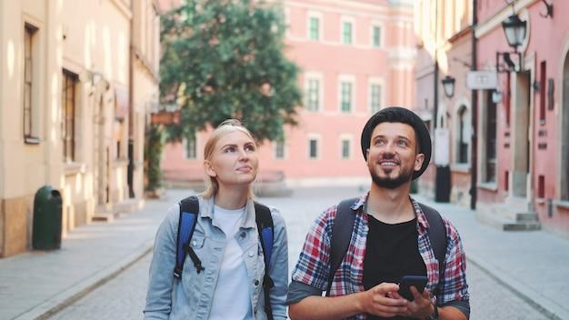 Młoda para turystów spaceru na ulicy i robienie zdjęć na smartfonie