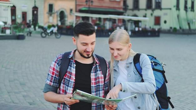 Młoda para turystów z mapą szukająca nowego historycznego miejsca w centrum miasta