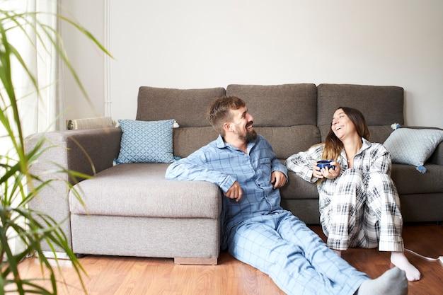 Młoda para ubrana w piżamę w domu. są szczęśliwi i śmieją się na wakacjach, cieszą się byciem razem.