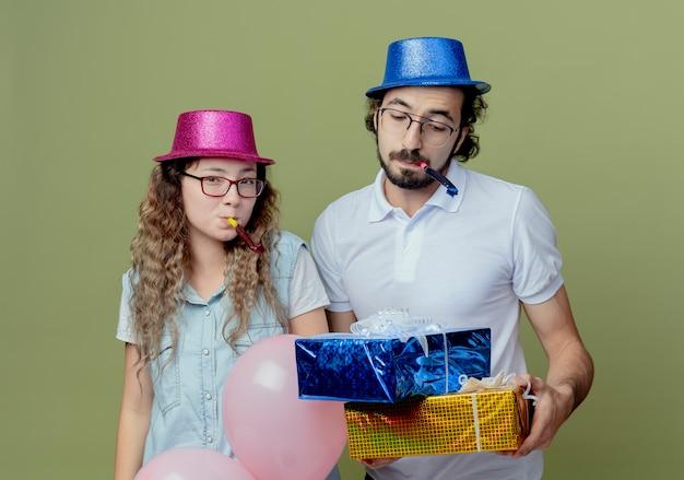Młoda para ubrana w różowy i niebieski kapelusz dmuchanie w gwizdek i facet trzyma i patrząc na pudełka na prezenty na białym tle na oliwkowej ścianie