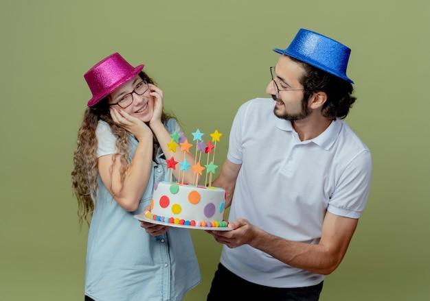 Młoda para ubrana w różowy i niebieski kapelusz uśmiechnięty facet daje tort urodzinowy radosnej dziewczynie odizolowanej na oliwkowej zieleni