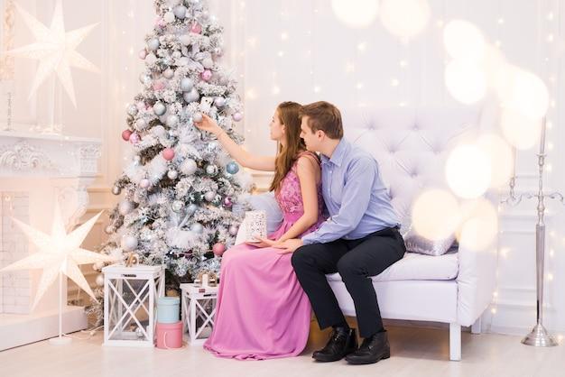 Młoda para udekoruje choinkę. mężczyzna i kobieta w pokoju bożonarodzeniowym fantazyjne ubrania na boże narodzenie.