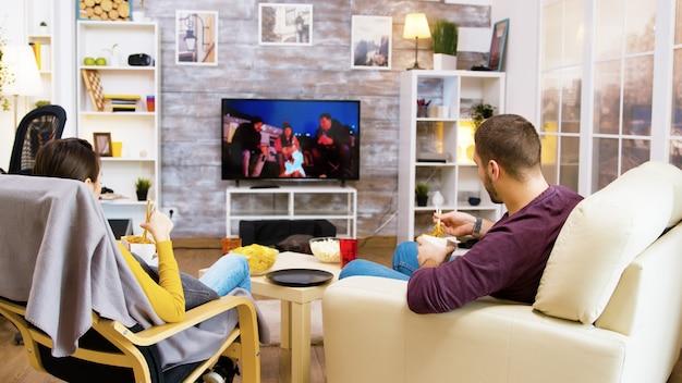 Młoda para uśmiecha się podczas oglądania telewizji, siedząc na kanapie, jedzenie popcornu.