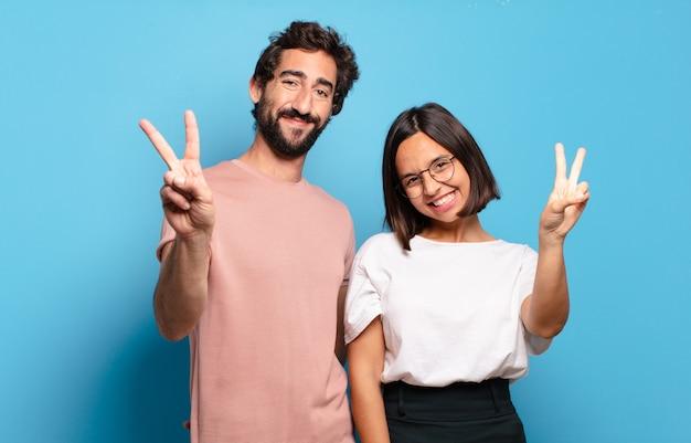 Młoda para uśmiechnięta i wyglądająca przyjaźnie, pokazująca numer dwa lub drugi z ręką do przodu, odliczając w dół