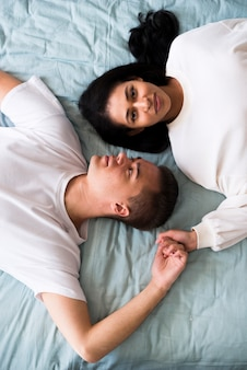 Młoda para w białe szaty leżące na łóżku łeb w łeb i trzymając się za ręce