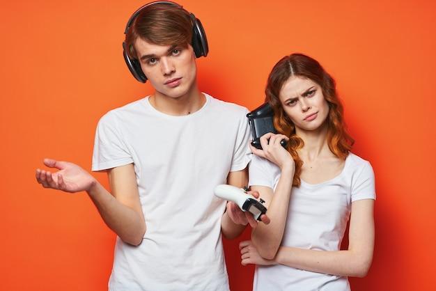 Młoda para w białych koszulkach z joystickami grająca na pomarańczowym tle konsoli