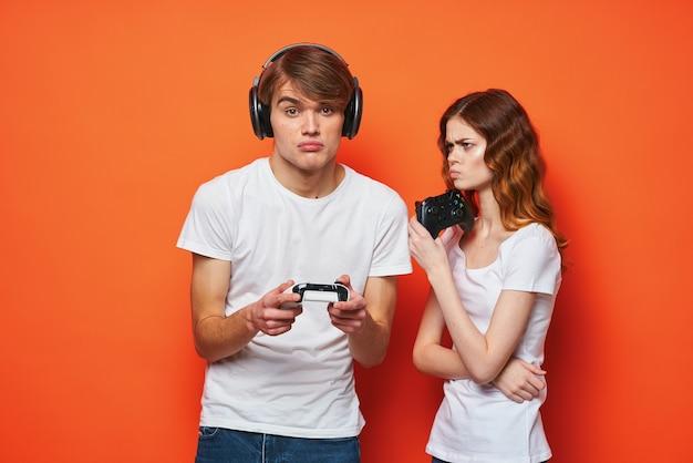 Młoda para w białych koszulkach z joystickami w ręce gra przyjaźń pomarańczowy tło. zdjęcie wysokiej jakości