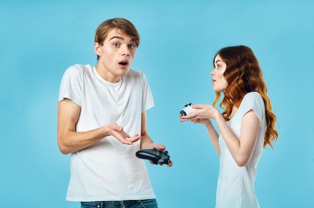 Młoda para w białych koszulkach z joystickami w rękach rozrywka w grach wideo