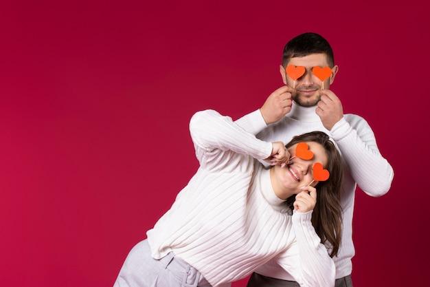 Młoda para w białych swetrach trzyma ręcznie robione czerwone serca zamykające oczy. czerwone tło