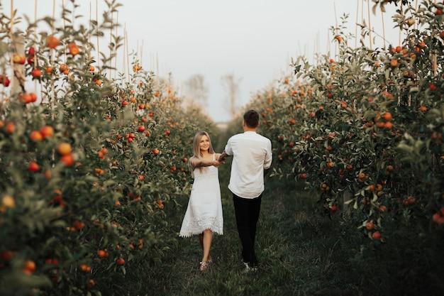 Młoda para w białych ubraniach krąży w ogrodzie jabłek. kobieta trzymająca się silnych dłoni swojego mężczyzny.