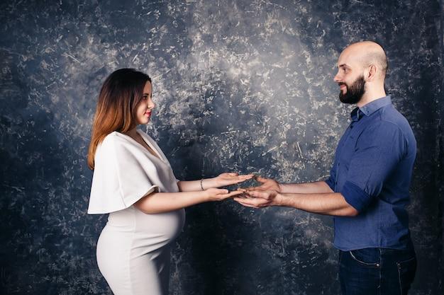 Młoda para w ciąży trzymając copyspace na dłoni.