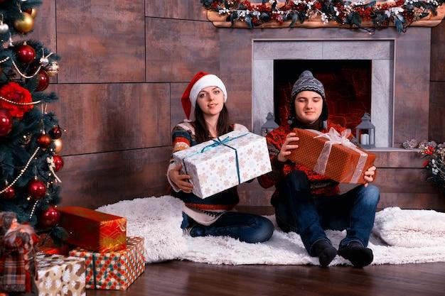 Młoda para w ciepłych swetrach i śmiesznych czapkach zimowych daje prezenty siedząc na dywanie przed choinką w salonie
