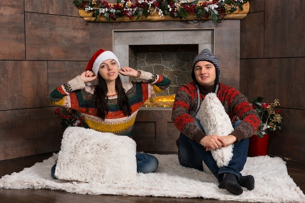 Młoda para w ciepłych swetrach i zabawnych zimowych czapkach siedzi na dywaniku przed udekorowanym kominkiem