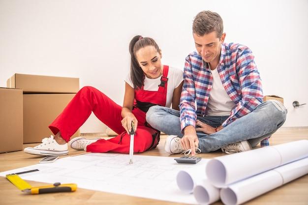 Młoda para w codziennych ubraniach i ogólny plan dekoracji mieszkania na papierowych planach.