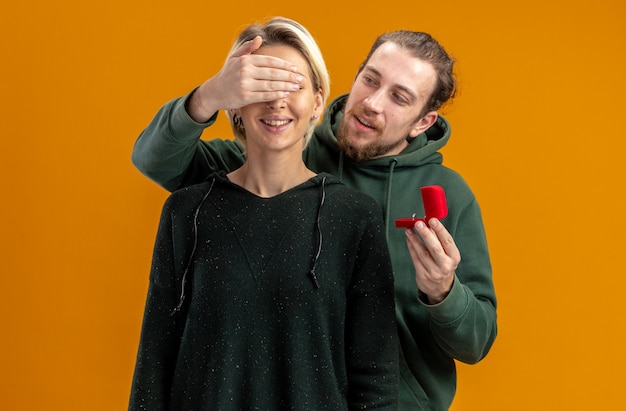 Młoda para w codziennych ubraniach szczęśliwy mężczyzna składający propozycję z pierścionkiem zaręczynowym w czerwonym pudełku zakrywającym oczy jego zdumionej i zaskoczonej dziewczyny koncepcja walentynki stojąca na pomarańczowym tle