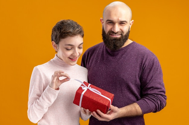 Młoda para w codziennych ubraniach uśmiechnięty brodaty mężczyzna daje prezent swojej zaskoczonej i szczęśliwej dziewczynie świętującej walentynki stojącej na pomarańczowym tle
