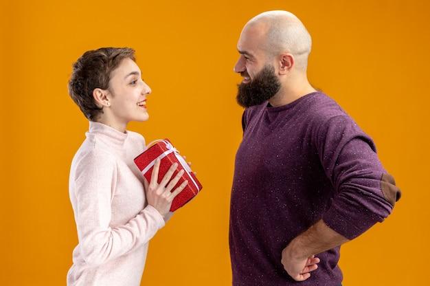 Młoda para w codziennych ubraniach uśmiechnięty brodaty mężczyzna daje prezent swojej zaskoczonej i szczęśliwej dziewczynie świętującej walentynki stojącej nad pomarańczową ścianą