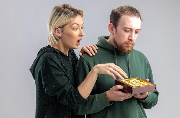Młoda para w codziennych ubraniach zaskoczona kobieta patrząc na pudełko z czekoladkami w rękach jej poważnego chłopaka świętującego walentynki stojącego nad białą ścianą