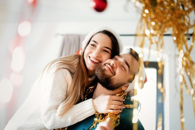 Młoda para w czapkach świątecznych ozdabia dom na boże narodzenie i nowy rok