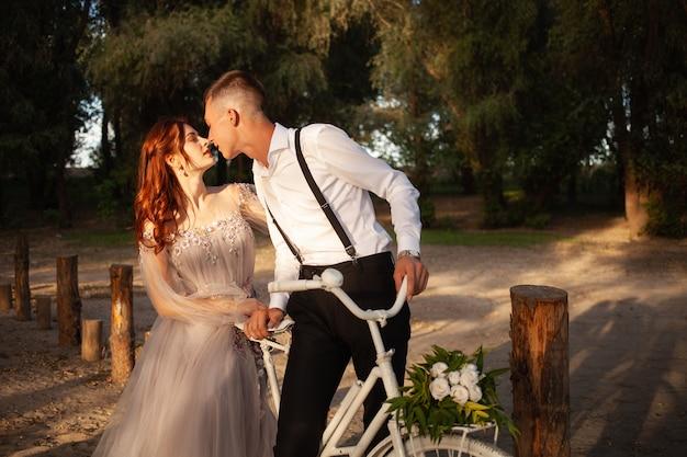 Młoda para w dniu ślubu z rowerem