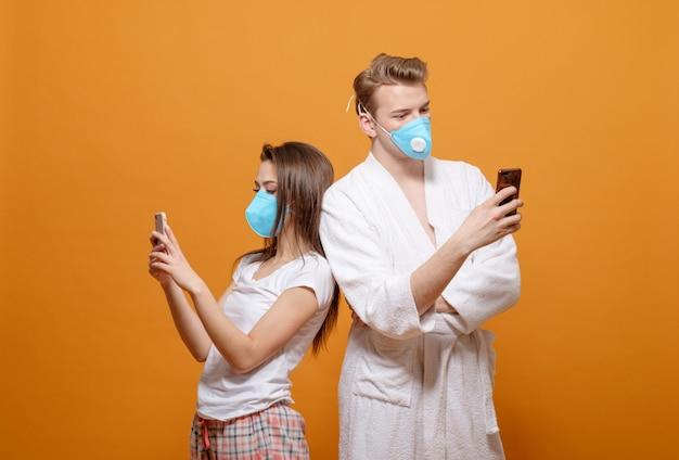 Młoda para w domu ubrania na ścianie pomarańczowy za pomocą swoich telefonów komórkowych