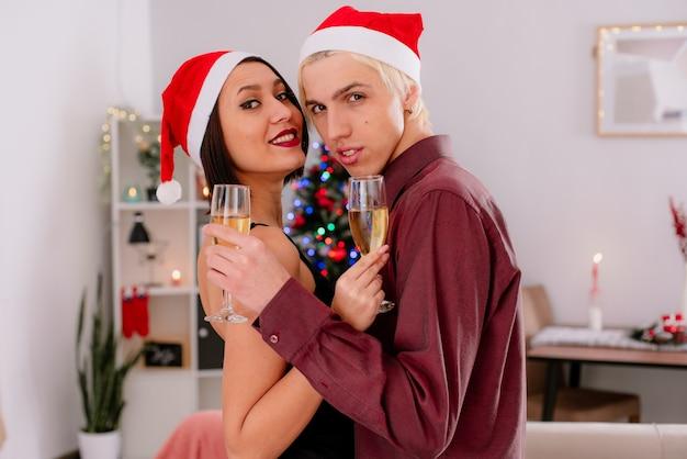 Młoda para w domu w czasie świąt bożego narodzenia pewny siebie facet i uśmiechnięta dziewczyna w czapce mikołaja stojąca przed sofą w salonie z kieliszkiem szampana tańcząca