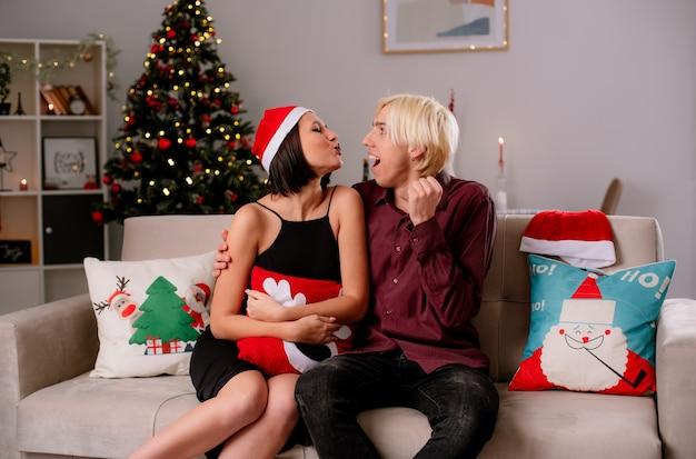 Młoda para w domu w czasie świąt bożego narodzenia w czapce mikołaja siedzi na kanapie w salonie dziewczyna trzyma świąteczną poduszkę robi gest pocałunku facet patrzy na nią robi gest tak