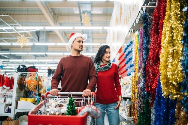 Młoda para w dziale dekoracji świątecznych w supermarkecie