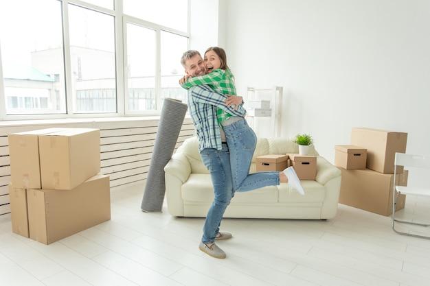Młoda para w dżinsowych spodniach w objęciach radości w swoim nowym mieszkaniu podczas przeprowadzki. koncepcja