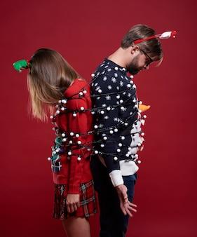 Młoda para w dziwnych ubraniach świątecznych związanych z lampkami bożonarodzeniowymi
